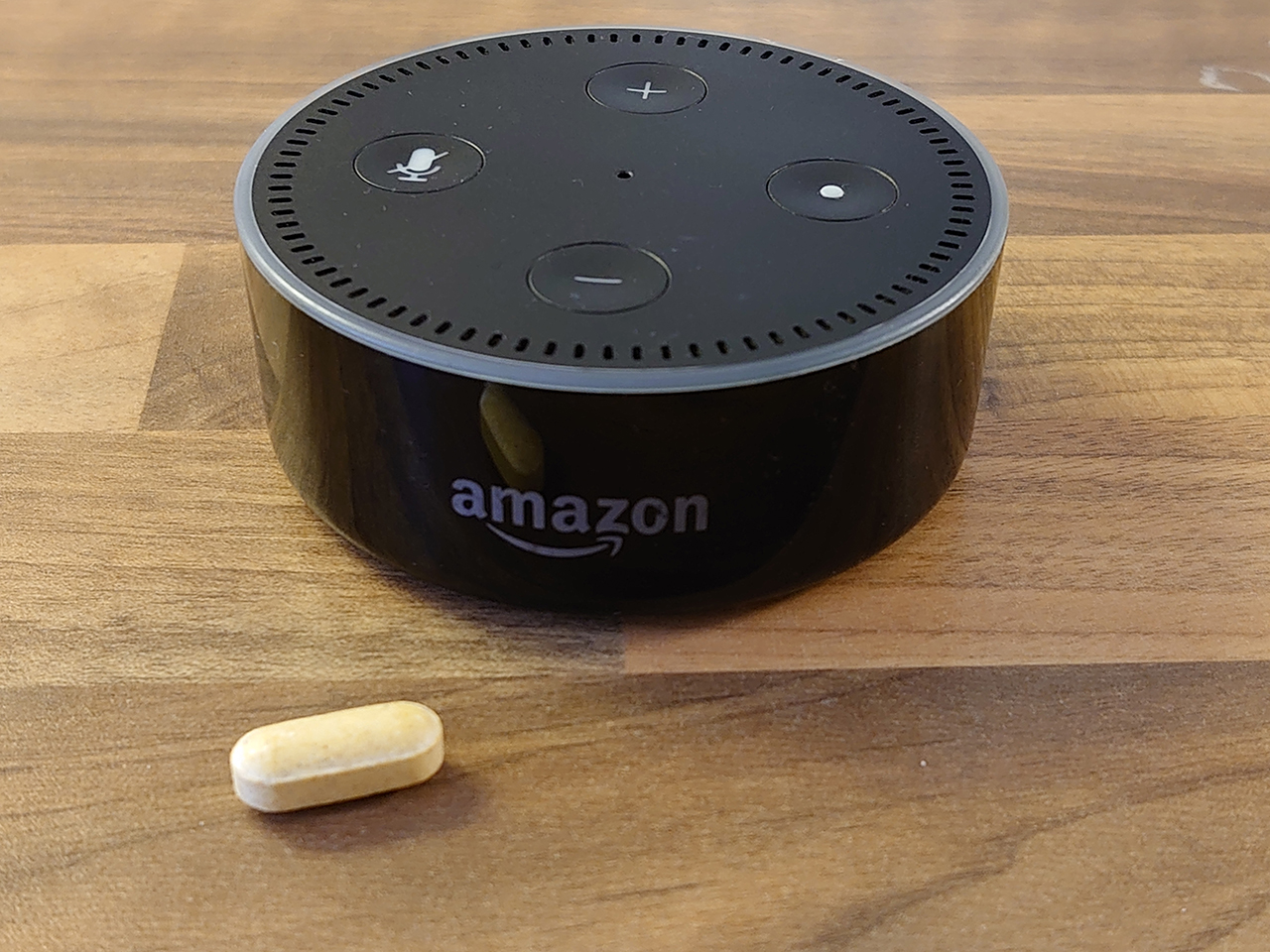 Amazon Dot running Alexa next to a pill
